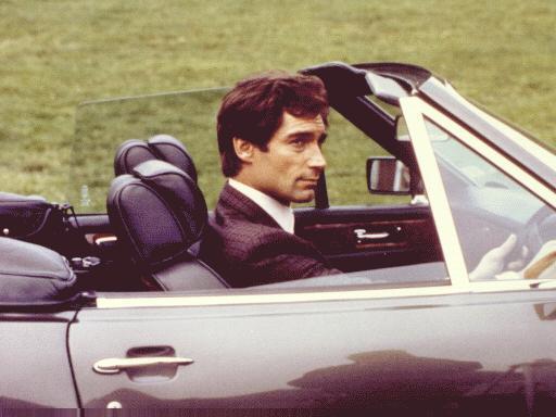 James Bond spelad av Timothy Dalton i sin tjänstebil, en Aston Martin V8 Volante med manuell låda från mitten av 80-talet.