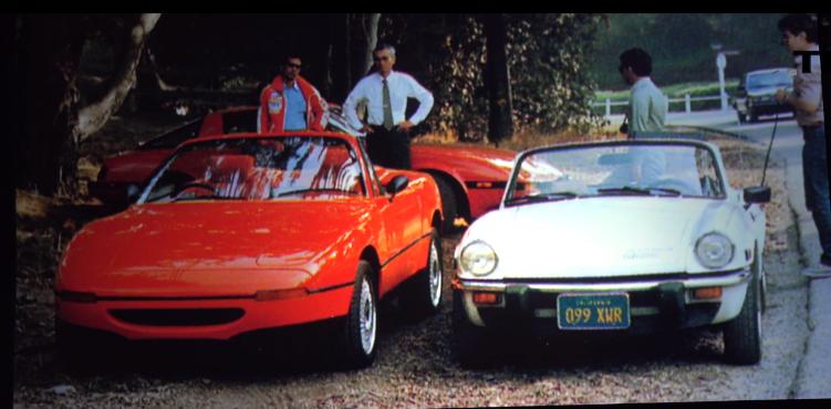 Ett fantastiskt foto av Yamamoto som övervakar testandet av en Miata-prototyp i Kalifornien. Bredvid står den största inspirationskällan, en Triumph Spitfire. I bakgrunden den snygga sportbilen Mazda RX7.